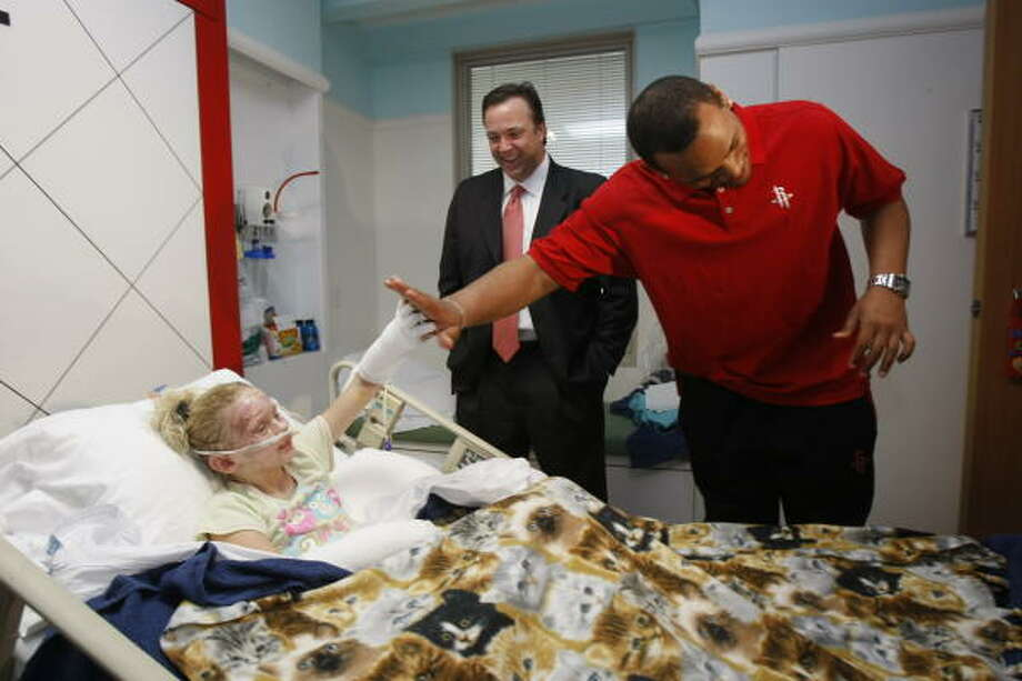 Rockets forward Chuck Hayes, right, gives a high-five to burn patient Makayla Henson, 10, left, as Rockets CEO Tad Brown looks on inside Henson's hospital room at Children's Memorial Hermann Hospital on Friday. Hayes and Brown were at the hospital as part of the grand opening of the Rockets Lounge, where teenage patients there can have a modern, sophisticated place of their own to watch TV and movies, work on the computer, read, relax and socialize. Photo: Julio Cortez, Chronicle