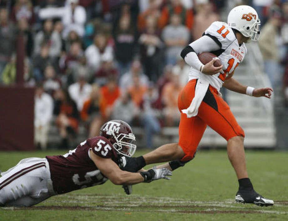 Texas A&M defensive tackle Matt Moss is unable to bring down Oklahoma State quarterback Zac Robinson. Photo: Julio Cortez, Chronicle