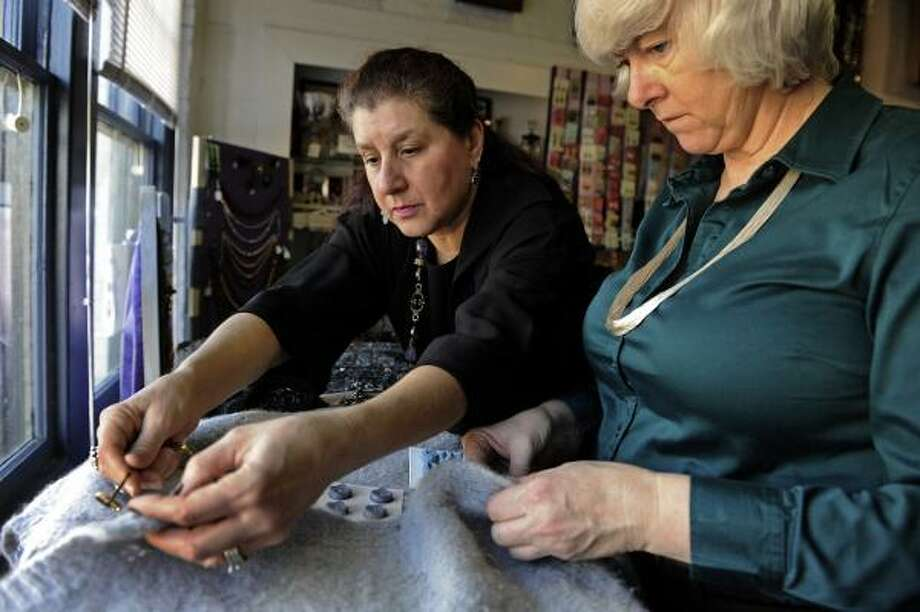 Elinor Coleman, left, helps Cathy Willis select buttons to update two sweaters. As the economy declines, more people find ways to make do with their old clothes. Photo: Washington Post