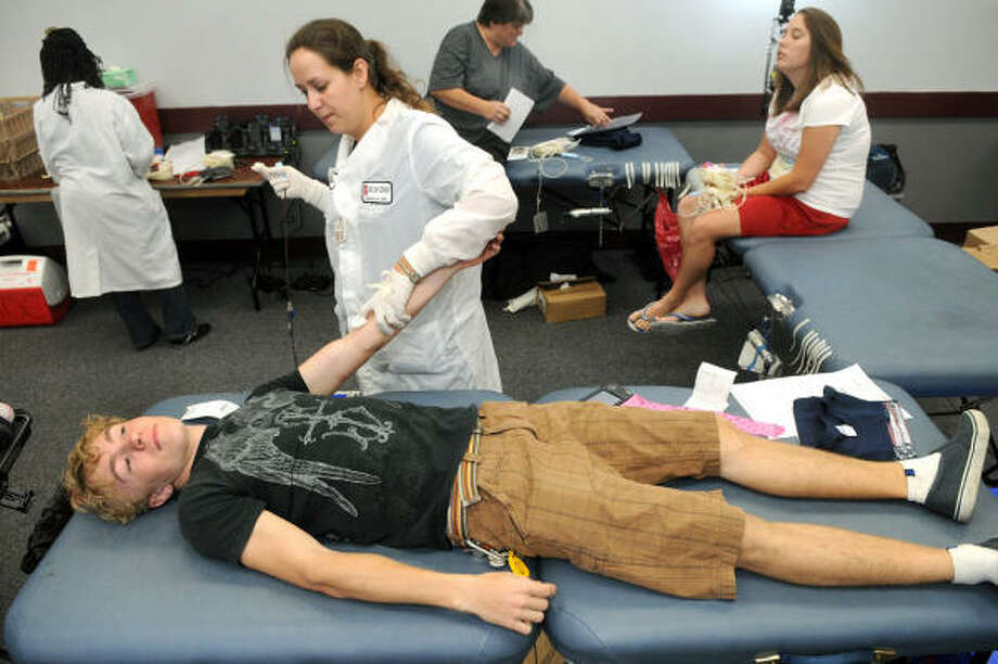 GIVING OF HIMSELF: Kenny Chamberlin, 18, a 2009 graduate of Atascocita High School, with help from Jessica Watts, of Angleton, from the Gulf Coast Regional Blood Center, finishes up his blood donation at the Humble Civic Center during the blood drive to benefit Grant Mctaggart, a young Kingwood boy, who was diagnosed with a rare form of leukemia in May. Photo: Jerry Baker, For The Chronicle