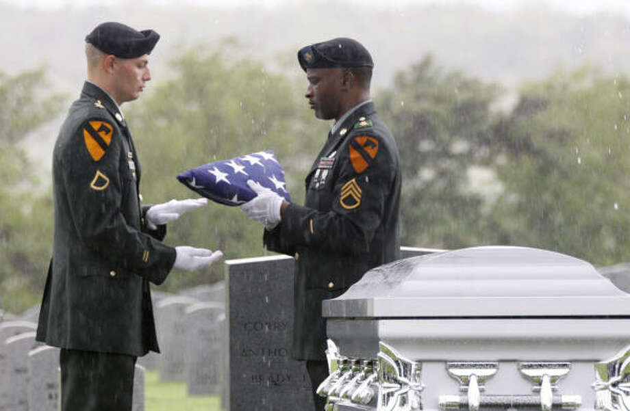 One of the ceremonial flags is presented at a coffin containing remains of seven National Guardsmen killed in Iraq during an interment ceremony at the Dallas-Fort Worth National Cemetery on Sunday. Photo: RON T. ENNIS, FORT WORTH STAR-TELEGRAM