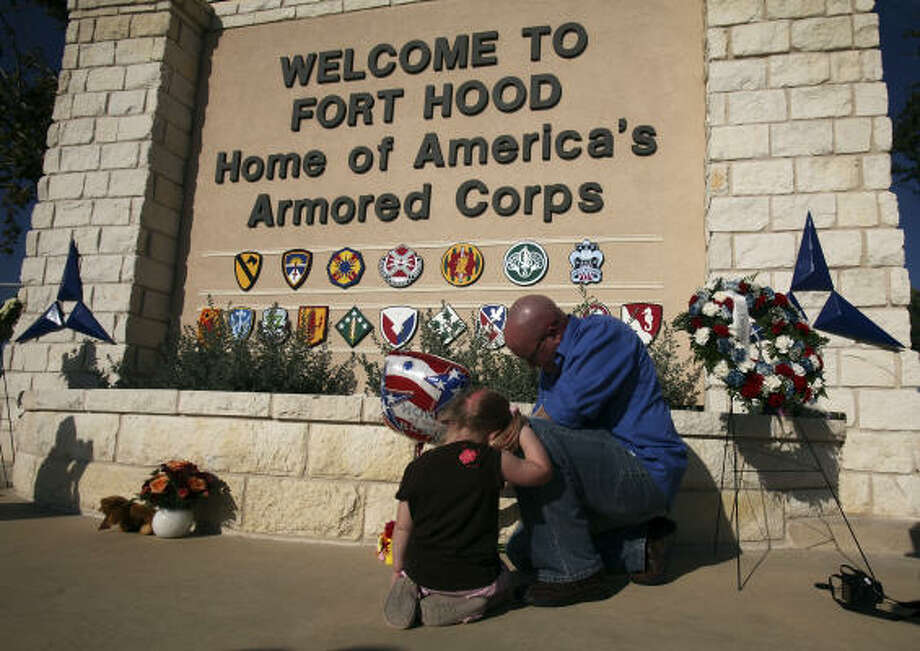 U.S. Army Spc. Ryan Hill and his daughter Emma, 3, light a candle at Fort Hood on Saturday to remember the shooting victims. Photo: EDWARD A. ORNELAS, SAN ANTONIO EXPRESS-NEWS