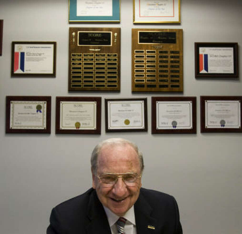Bob Ashfield, 75, a volunteer with  SCORE, displays some of the plaques and awards given to the Houston office. He is one of the many retirees helping people get information on starting a business.  Photo: Johnny Hanson, Chronicle