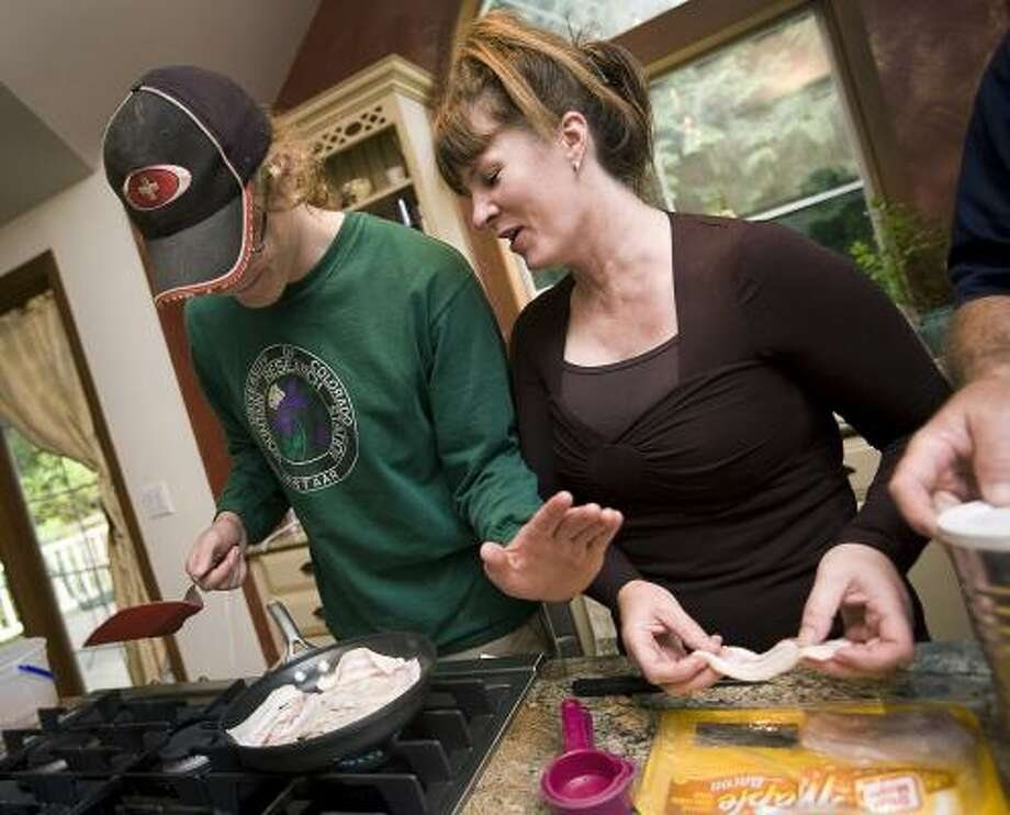 ReSTART center co-founder Cosette Dawna Rae helps client Ben Alexander, of Iowa City, Iowa, cook bacon at the program's facilities in Fall City, Wash. Alexander said the Internet took over his life. Photo: STEPHEN BRASHEAR, Associated Press