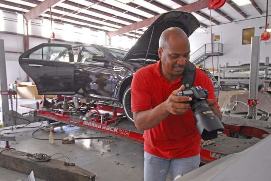 Chris Franklin checks out his photos during the Houston Photowalk photo session at the Elite Collision Paint & Body shop. Photo: Tony Bullard, For The Chronicle