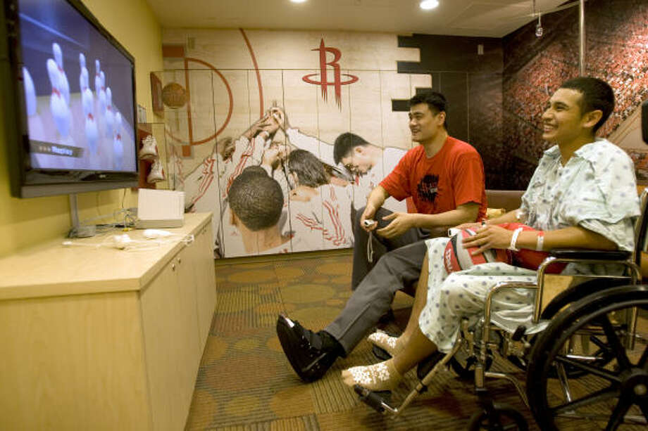 Sidelined center Yao Ming (left, with walking boot visible) shares a laugh with Alex Saldierna, 17, during a visit to Children's Memorial Hermann Hospital. Photo: Brett Coomer, Chronicle