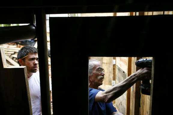 Jared Gamble, left, and Dan Phillips hang a homemade door at the Bone House. The house is made from materials that were bound for the trash.
