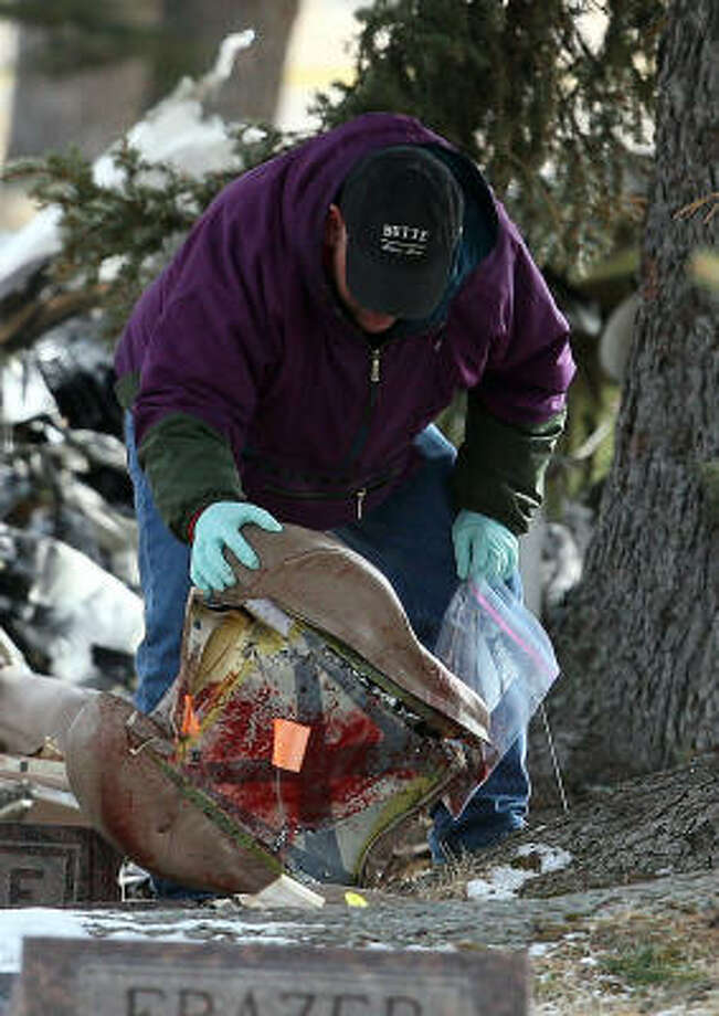 At Holy Cross Cemetery on Tuesday, an investigator examines a bloody seat cushion from the single-engine plane that crashed near Butte, Mont., Sunday. Photo: Michael Albans, Associated Press