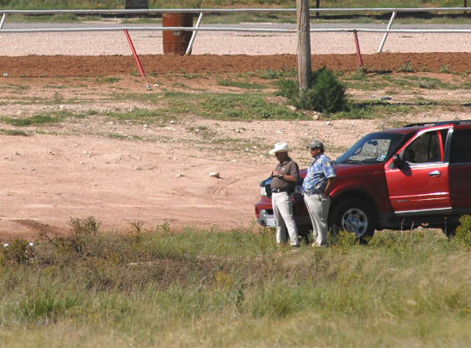 "Carl Rogers, left, chief investigator for the Ector County Medical Examiner's Office and ""J.C."" Cazares, owner of JC's Playground Racetrack south of Odessa examine the area of standing water where five people died in a truck Sunday evening Photo: Mark Sterkel, AP"