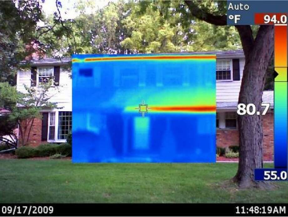 ENERGY CHECKUP: An infrared image showing the front of Katherine Salant's house. The yellow/red in the infrared area of the picture shows where the sun was shining on the house. The blue areas are shaded by trees and a front porch roof. Photo: Nathan Munson