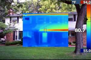 ENERGY CHECKUP: An infrared image showing the front of Katherine Salant's house. The yellow/red in the infrared area of the picture shows where the sun was shining on the house. The blue areas are shaded by trees and a front porch roof.