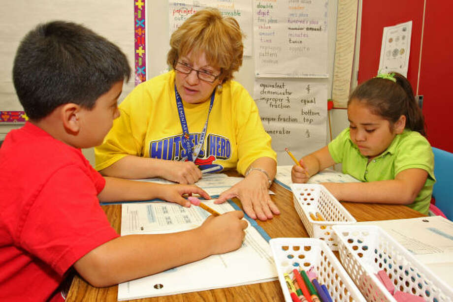 """Karen Stuessel, center, teaches a math intervention class for third-graders at Hutsell Elementary School in the Katy Independent School District. Classmates are Cesar Santoyo, left, and Vanessa Garcia. The Texas Education Agency rated the school in 2008 as """"exemplary."""" Between 2005-07, the school was designated """"academically acceptable."""" Photo: Suzanne Rehak, For The Chronicle"""