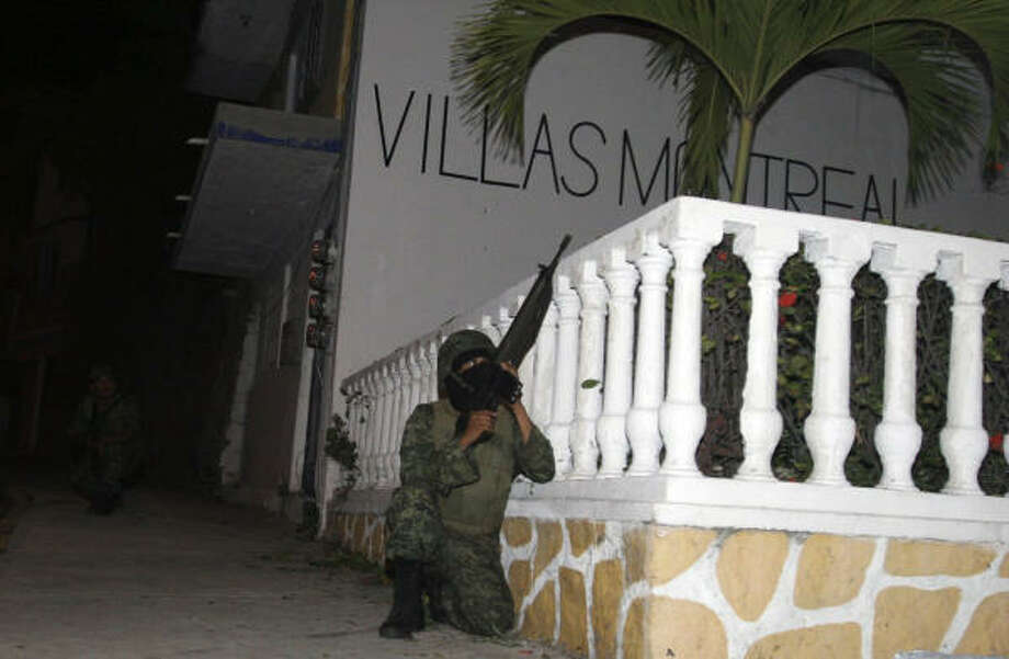 Soldiers hold a position during the gunfight in Acapulco, Mexico, on Saturday in a tourist area frequented by Americans on cruise ships and residents of Mexico City and its suburbs. Photo: AP
