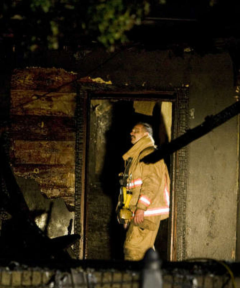 A firefighter works Thursday at 12th Street and Herkimer in the Heights. Photo: Smiley N. Pool, Chronicle