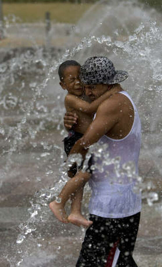 Gabriel Smiley, 3, gets a lift Tuesday through a Discovery Green fountain from David Sandoval, a family friend. Tuesday was sunny, but rain clouds are rolling in.  Photo: Johnny Hanson, Chronicle