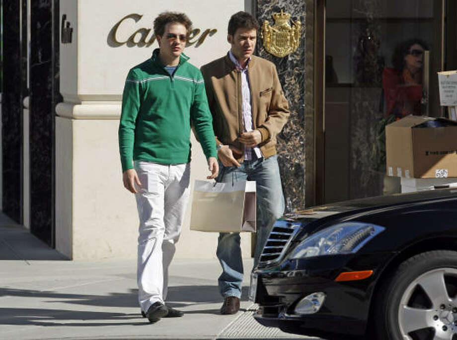 NO LABEL: A shopper carries a plain bag past Cartier and other upscale stores and cars on Rodeo Drive in Beverly Hills, Calif. Photo: Reed  Saxon, AP