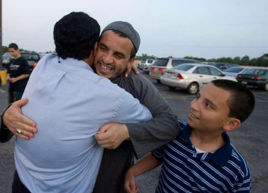 As Ilies Bouchikhi, 12, looks on, his father, Sheikh Zoubir Bouchikhi, hugs a member of the Abu Bakr Siddqui mosque. Photo: Billy Smith II, Chronicle