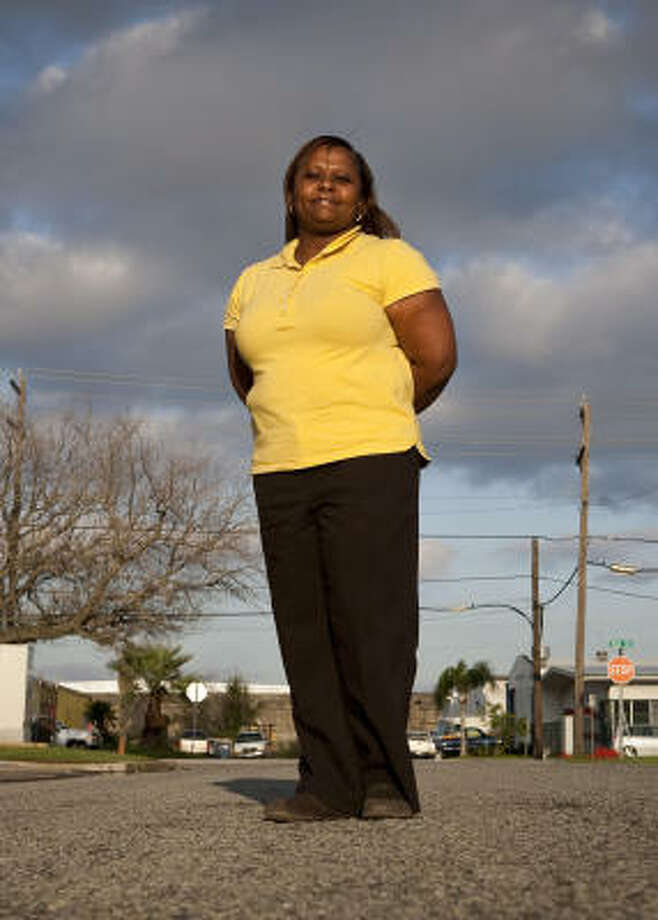 Verneia Shaw, standing on the street at the site of her former public housing apartment in Galveston, works full time as a clerk for Galveston County and attends college. Shaw, who now lives in League City, will lose federal aid that helps pay her rent at the end of March. Photo: Nathan Lindstrom, Chronicle