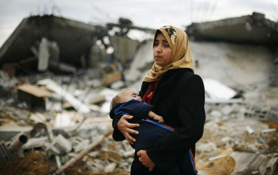 A BLEAK OUTLOOK: Palestinian Tahani Hijji, 26, carries her young child Tuesday as she inspects her destroyed house in the southern part of Gaza City. Hamas leaders vowed to restore order, but reconstruction faced problems of renewed fighting and Israel's control over border crossings. Photo: Anja Niedringhaus, AP