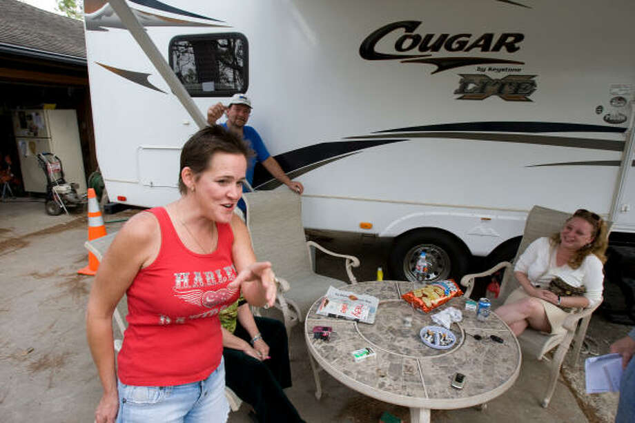 Nancy Schnell and neighbors share a laugh in Shoreacres over the story of trouble in delivering a FEMA trailer. Photo: Nick De La Torre, CHRONICLE