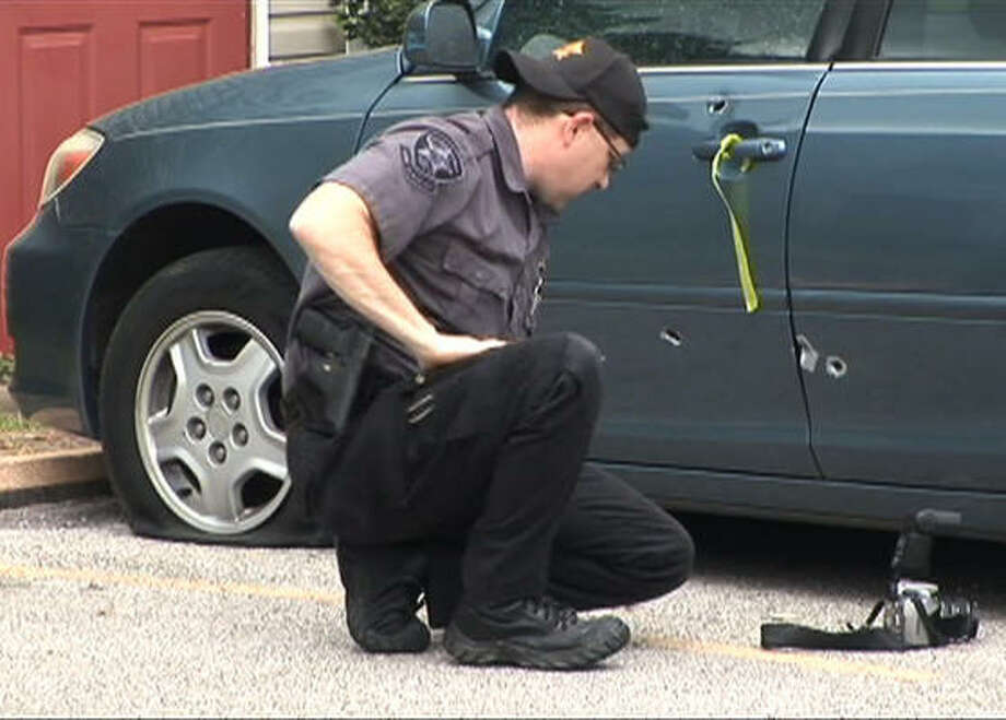 An Alvin police investigator surveys a car damaged during the standoff. Photo: Jason Witmer, Chronicle