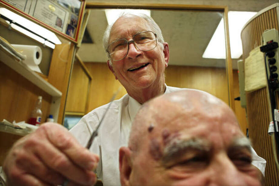 Al Stem cuts the hair of engineer Gerald Harris, who has been coming to Stem for seven years. Stem has been cutting hair since 1970 under the El Paso Building. Photo: Eric Kayne :, For The Chronicle