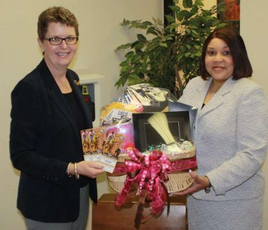 Lamar Educational Awards Foundation Executive Director Janice Knight holds three tickets to the Jonas Brothers concert at the Houston Livestock Show and Rodeo, while Pink Elementary Principal Chandra Woods shows off the basket her campus is providing for the silent auction at Men Who Cook 2009. Photo: Courtesy, LCISD