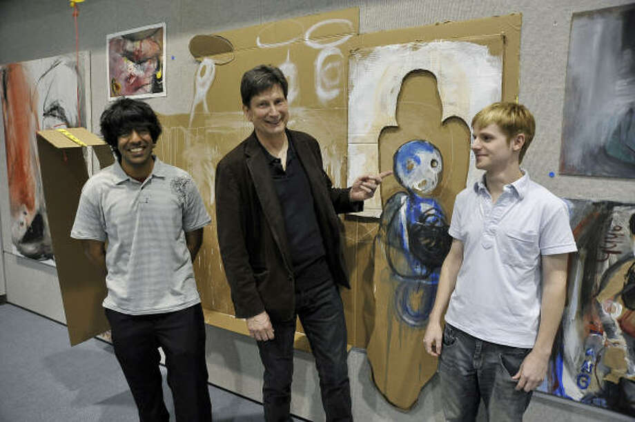 "CUTLINE: San Jacinto College art professor Martin Wnuk , center, is flanked by two students who created art for the ""Angels and Anarchy"" exhibit. Zain Awais, left, and Daniel Shanks are shown displaying an untitled work that the two students collaborated to create. Photo: Rob Vanya, For The Chronicle"