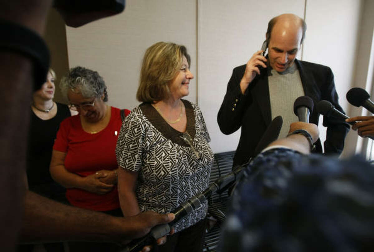 Andy Kahan of the crime victims assistance center at Mayor Bill White's office, talks on the phone to Farah Fratta's father, Lex Baquer, about the Saturday verdict in the case of Robert Fratta.