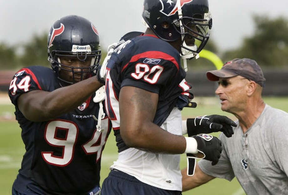 The fiery Bill Kollar (right) can scream, yell and goad with the best of them, as Antonio Smith (left) learned during one of the first practices of training camp last week. Photo: Brett Coomer, Houston Chronicle