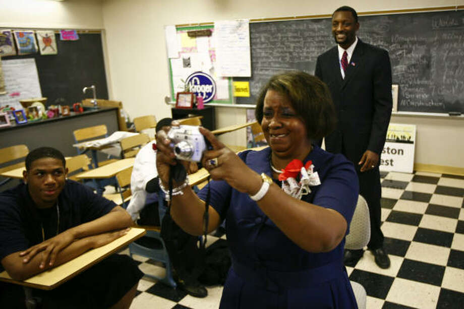 Sharron Solomon, a teacher at Booker T. Washington High School, snaps a picture of President Barack Obama during the televised inauguration ceremony Tuesday. At left is student Javenta Jackson, and Principal Mark Bedell is at right. Photo: Michael Paulsen, Chronicle