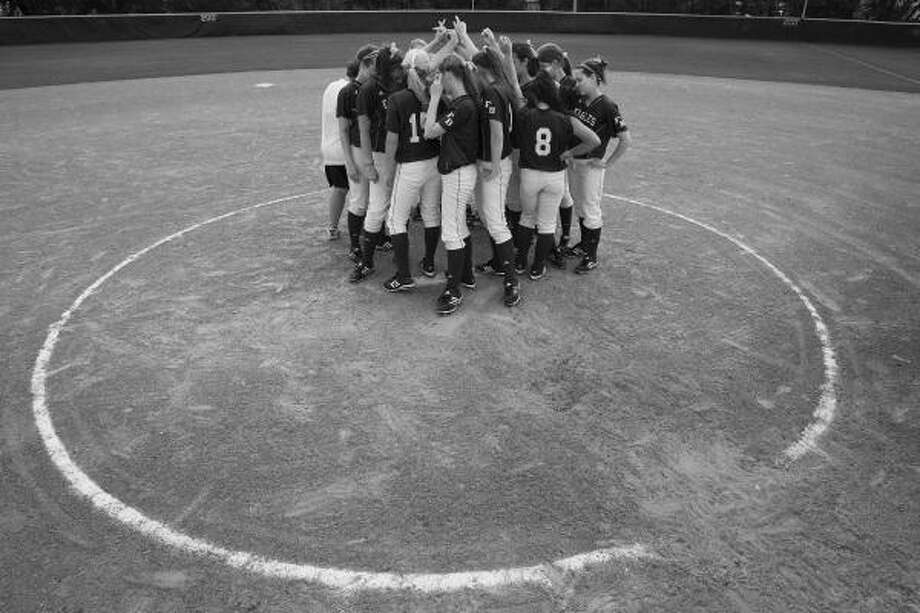 The Fort Bend Baptist Academy girls softball team circles in prayer. Photo: Smiley N. Pool, Chronicle