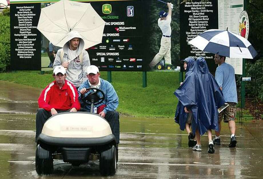Volunteers and spectators make their way through the rain at TPC Deere Run during a weather delay Friday. Photo: Larry Fisher, AP