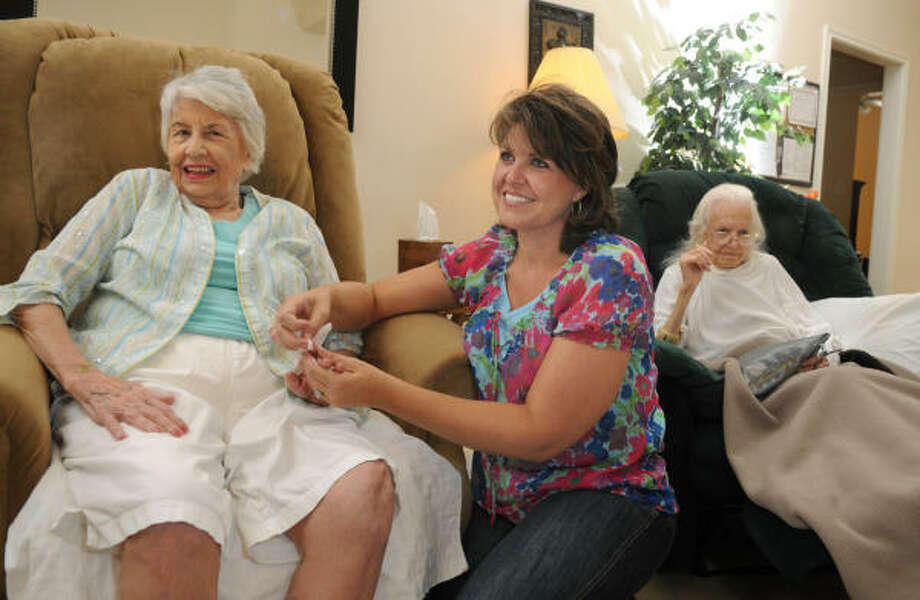 PERSONAL ATTENTION: Terri Buckholtz, right, owner of Unlimited Care Personal Care Cottages in The Woodlands, visits with resident Pat Kamman. Photo: Jerry Baker, For The Chronicle