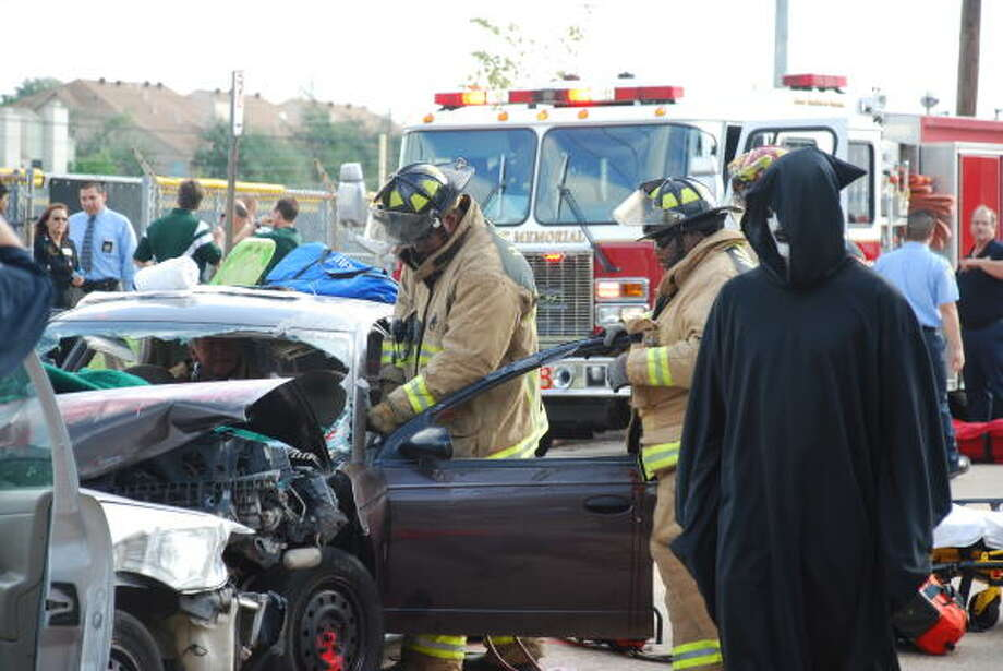 GRIM EVENT: The Grim Reaper, portrayed by Stratford High science teacher Dave Avis, walks around the mock DWI wreckage scene while firefighters from station No. 78 try to 'save' the lives of students in the wreckage on Oct. 8. Avis spent the school day pulling students out of classrooms every 15 minutes, signifying the rate at which people die from drunk driving accidents. Photo:  Bibi Rajeh/Stratford High, COURTESY PHOTO :