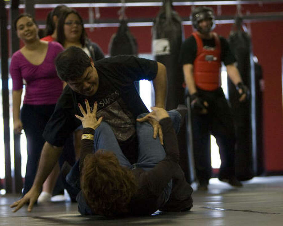Instructor Nino Castandiello simulates an attack on student Bea Lombrana during the self-defense class Saturday. Photo: James Nielsen, Chronicle