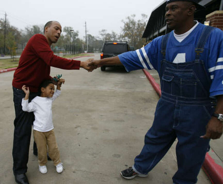 Ronald Green stops to shake hands with a voter as he and his son Christopher, 4, make their way into Thompson Elementary School, where he voted on Saturday. Photo: Karen Warren, Chronicle