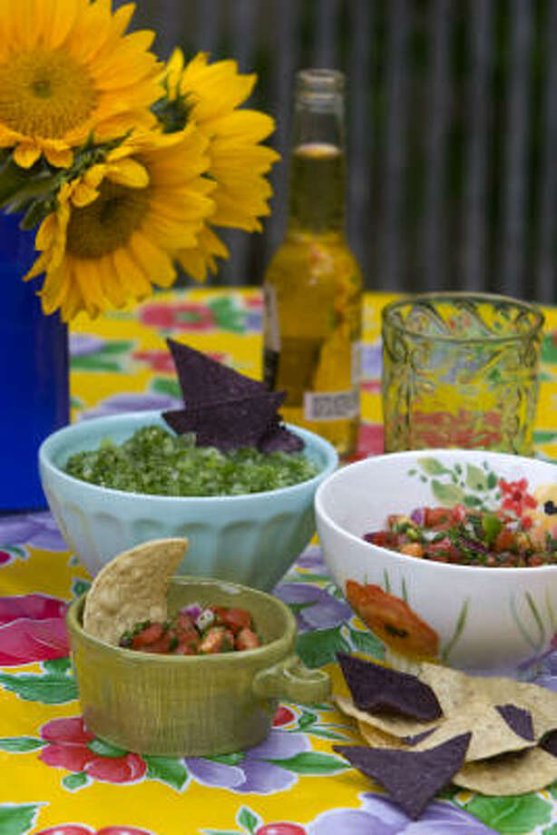 Stylish bowls set a festive tone. Zachary bowl in green, $6.95, Pier 1 Imports; sky-blue latte bowl, $4, and Verdant Acres bowl, $10, Anthropologie; on Mexican oilcloth, $28, Surroundings. Below, pea pod dip bowl, $7, Pier 1 Imports. Photo: Johnny Hanson, Chronicle