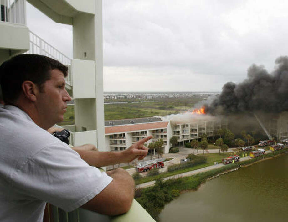 John Baker of Tupelo, Miss., watches the fire from a nearby condo unit. Photo: Kevin M. Cox, Galveston Daily News
