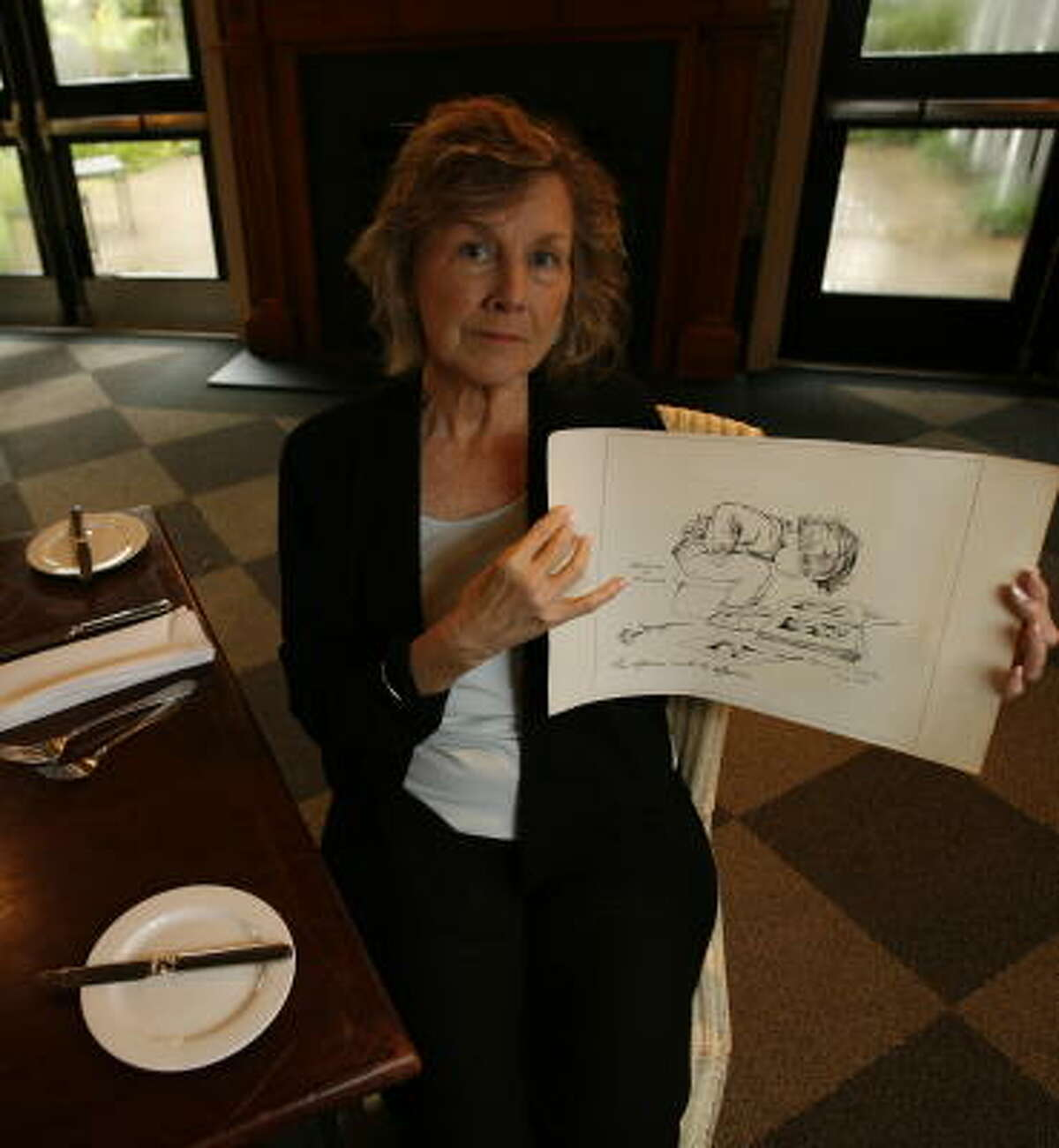 Elouise Adams Jones, owner of Ouisie's Table in Houston, holds a replica of an original print that was stolen from her restaurant. It once hung on the door of the women's rest room.