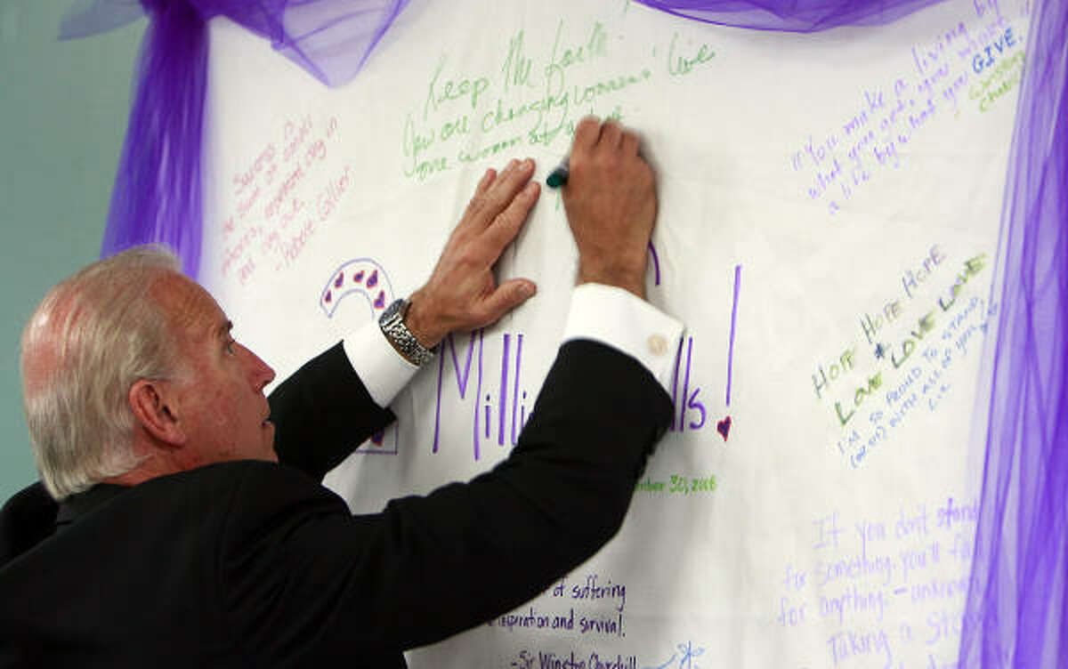 The vice president signs a card during a stop at a hotline for abused women in Austin. He went to Houston after his visit to the National Domestic Violence Hotline Headquarters.