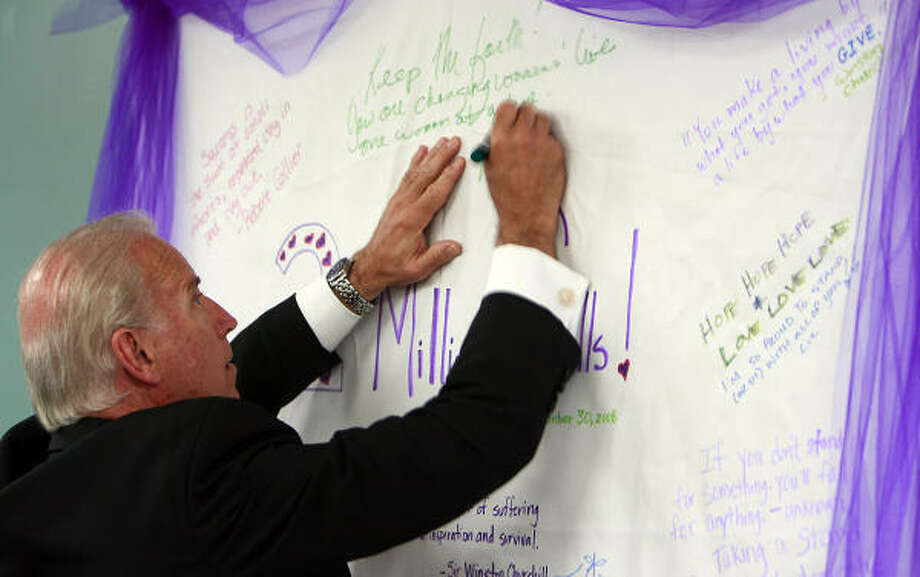The vice president signs a card during a stop at a hotline for abused women in Austin. He went to Houston after his visit to the National Domestic Violence Hotline Headquarters. Photo: Associated Press