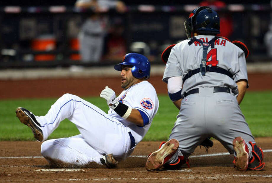 Mets catcher Omir Santos scores a fourth inning run past Cardinals catcher Yadier Molina. Photo: Jim McIsaac, Getty Images