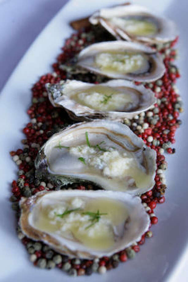 The warm oysters on the half shell appetizer at Tesar's is served in French Éschiré butter. Photo: Melissa Phillip :, Chronicle