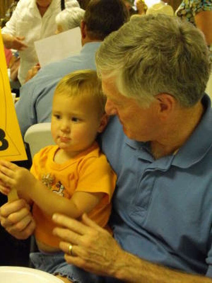 Kylie Sissom learns how to handle the auction paddle while sitting on the lap of her grandfather, Skip Conner. Photo: TRISH JOHNSON, FOR THE CHRONICLE