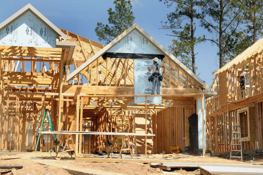 BUILDING CONTINUES: Framework goes up on two new homes in the Graystone Hills subdivision, at Park Boulevard and Longmire Road in Conroe. The rolling hills offer different elevations for homes. Photo: David Hopper, For The Chronicle