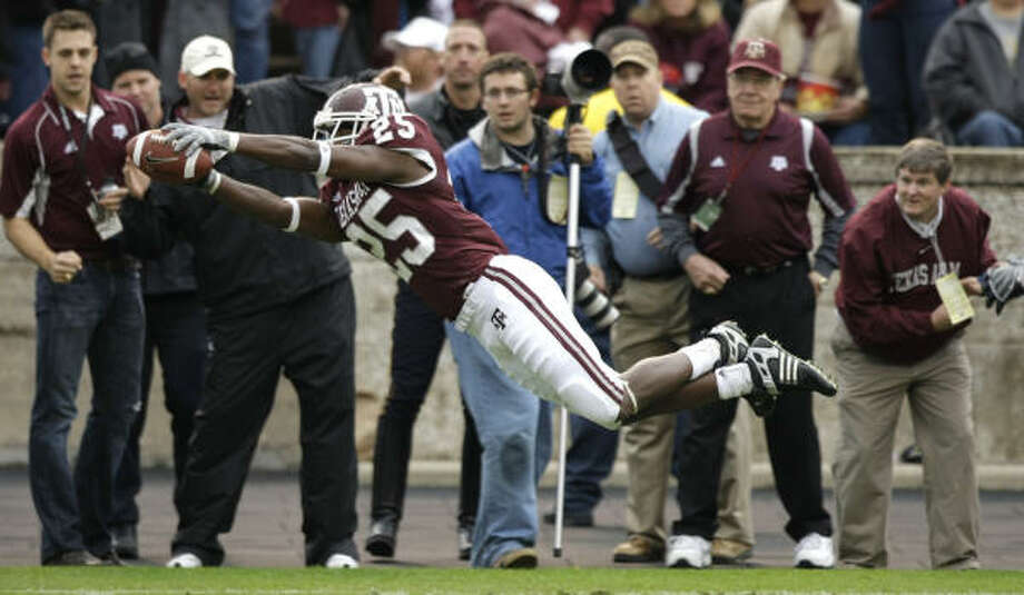 A&M cornerback Jordan Pugh dives for the end zone after intercepting a Nick Florence pass. Photo: Brett Coomer, Chronicle