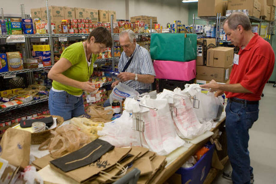 GETTING READY: West Houston volunteers Karen Burnley, Ken Bounds and Gary Hummel, sort donations for packing and delivery in the food pantry at West Houston Assistance Ministries. Photo: R. Clayton McKee, For The Chronicle