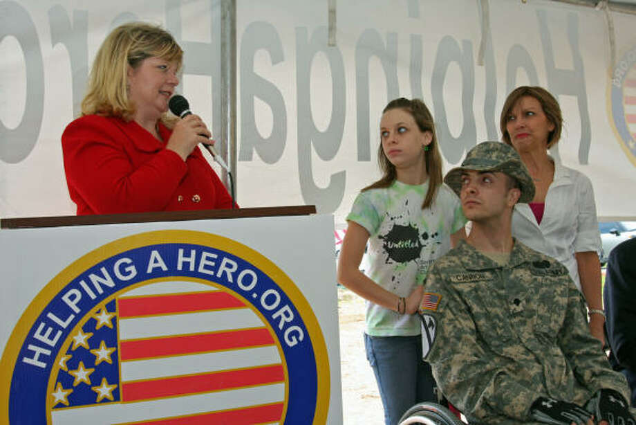Meredith Iler, national chairman, Home Program, of HelpingaHero.org. honors retired U.S. Army Specialist Dillon Cannon, 22. With him are his sister, Kelsey, 13, and mother, Patti Cannon. Photo: Suzanne Rehak, For The Chronicle