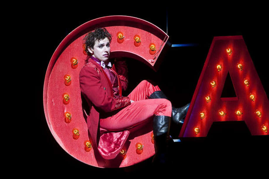 "Cabaret's Emcee (Leo Ash Evens) is lowered to the stage nestled in the ""Cabaret"" sign in TUTS' production. Photo: Bruce Bennett"